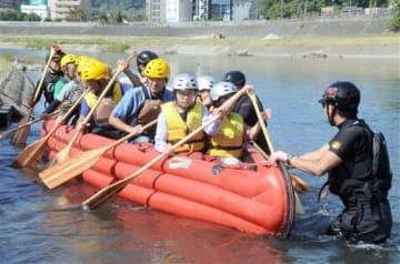 避難ボートに乗り、水害時の避難方法を学ぶ参加者たち=14日、熊本市