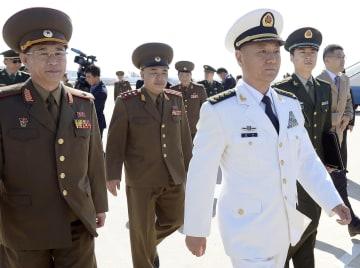 平壌国際空港に到着した中国中央軍事委の苗華政治工作部主任(手前右)=14日(共同)