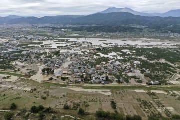 台風19号で千曲川(手前)の堤防が決壊し、流れ出た濁流で浸水したままの住宅地=14日午前10時35分、長野市(小型無人機から)