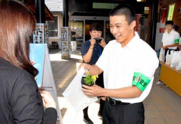 ビオラと防犯啓発チラシの入った袋をどんぶり館来場者に手渡す宇和高校の生徒