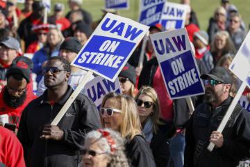 米ミシガン州にあるGM工場の外を行進する労働者と家族ら=13日(ゲッティ=共同)