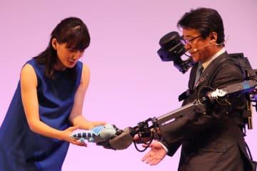 ぬいぐるみを「ウェアラブルアバター」と呼ばれるアバターロボットに手渡す綾瀬はるかさん(左)。右側はANAホールディングスの片野坂真哉社長