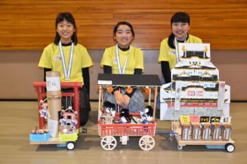 インドネシアで開かれる世界大会に出場する(右から)元明誠華、華衣さん姉妹と松山柚乃花さん。手前が出品される「からくりパフォーマンスカー」