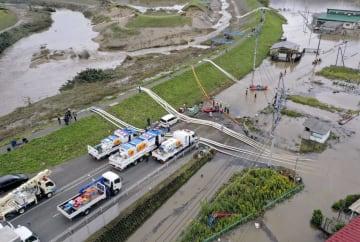 浸水した宮城県丸森町の中心部から川へ排水するポンプ車=14日(国土交通省東北地方整備局提供)
