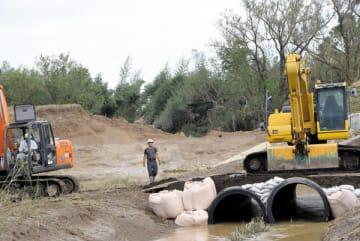決壊した都幾川の堤防を補修する重機=15日午後、東松山市早俣