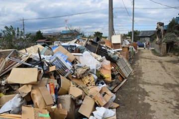 道路沿いに山積みされた、浸水で使えなくなった家財道具=15日午後、東松山市早俣