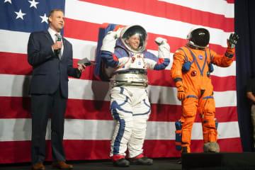 米航空宇宙局(NASA)が公開した宇宙服の試作品。月面探査用(中央)と宇宙船内用(右)=15日、米ワシントン(AP=共同)