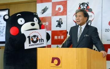 記者会見でくまモンのデビュー10周年の記念ロゴを紹介する熊本県の蒲島郁夫知事=16日午前、熊本県庁
