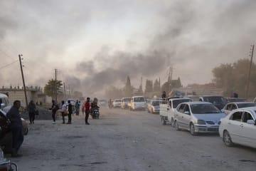 トルコ軍による砲撃から逃げる人びと(シリア北東部ラス・アル・アインで10月9日撮影)© AP Photo