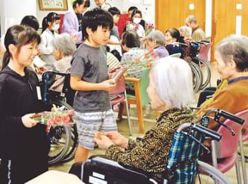 お年寄りに花束などを手渡す子どもたち(左)