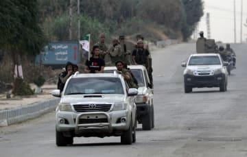 16日、シリア北部テルアビヤドで、車両で移動する、トルコが支援する反体制派の兵士(ロイター=共同)