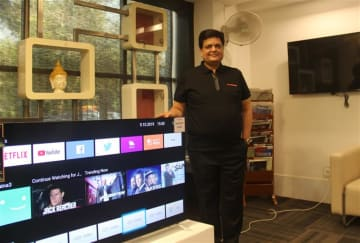 Pradeep Jain, managing director, Jaina Group, poses with a Sansui TV set at his company's headquarters in New Delhi on Oct. 9, 2019.