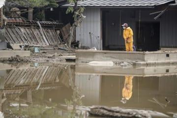 水害でたまった水の近くに立つ人=17日午前8時49分、長野市