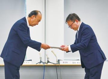 報告書を受け取る吉野教育長(左)