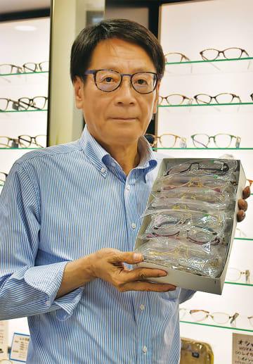 寄付予定の眼鏡を手にする中村代表