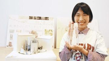 作品の横でトロフィーを持つ長橋さん