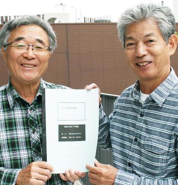 20周年の記念誌を手にする、根岸代表(左)と塚田幹夫副代表。市地域有形民俗文化財に登録されている、下倉田町の南谷の「大わらじ」も見学した
