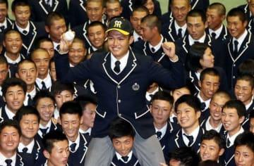 阪神から1位指名を受け、チームメートと喜ぶ西純矢=創志学園高