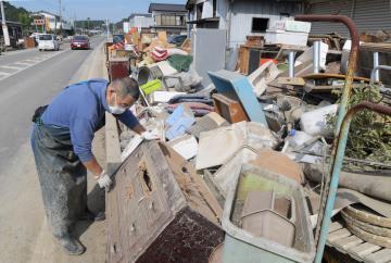 国道123号の歩道に積み上げられた災害ごみ=17日午前、水戸市藤井町、吉田雅宏撮影