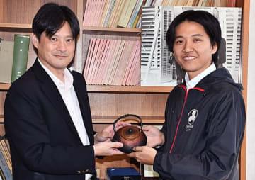 ブラックホールをイメージして製作した南部鉄器の急須を本間希樹所長に手渡す菊地海人さん(右)