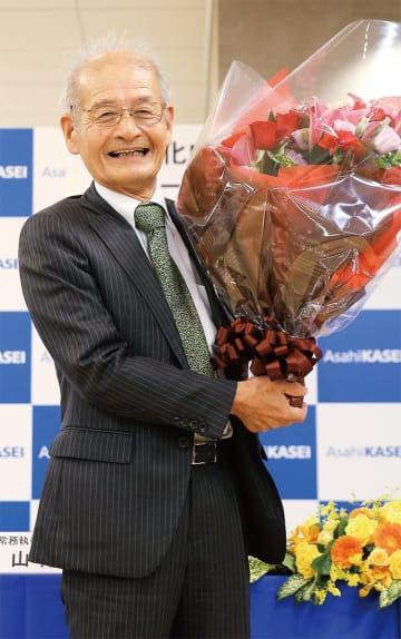 受賞が決まり花束を手に笑みを浮かべる吉野氏(=9日、旭化成本社/同社広報室提供)
