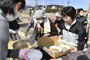 炊き出しの豚汁に並ぶ住民=16日午前11時52分、本宮市