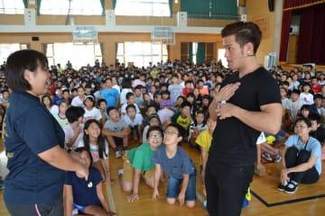 金城あかね先生(左)にトランプのカードを選んでもらうMASAさん=16日、宜野湾市のはごろも小学校