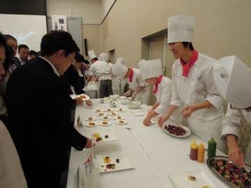 【三重県産食材を使ったメニューを提供する学生ら=津市一身田上津部田で】