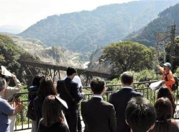 立野ダム展望所から建設現場を眺めるインフラ見学会の参加者。奥が北向谷原始林=南阿蘇村