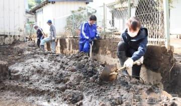 用水路にたまった土砂をかき出すボランティア=17日午後、富岡市内匠