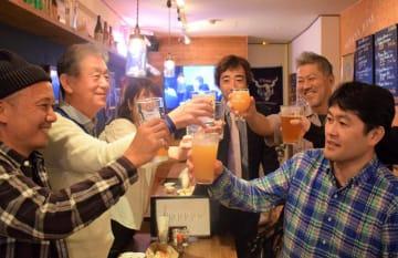 佐々木朗希投手の交渉権獲得が決まり、笑顔で乾杯をするファン=17日午後、千葉市美浜区のミハマベース