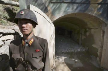 2018年5月24日、北朝鮮・豊渓里の核実験場で、爆破前の坑道入り口と朝鮮人民軍兵士(ゲッティ=共同)