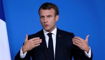 ブリュッセルで記者会見するフランスのマクロン大統領=18日(ゲッティ=共同)