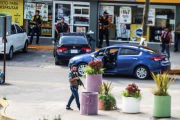 メキシコ北西部シナロア州クリアカンで治安当局と銃撃戦を展開する麻薬組織の男ら=17日(ロイター=共同)