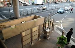 間仕切りの内側にあった吸い殻入れを外側に出した喫煙所。駅前ロータリーの乗降場所(右奥)や地下駐輪場への階段(中央左)に近いが、煙が漏れない措置は取られていない=三田市駅前町