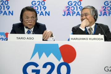 記者会見に出席した麻生太郎財務相(左)と日銀の黒田東彦総裁(右)=18日、ワシントン(AP=共同)