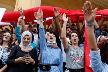 18日、ベイルートで経済状況の悪化に抗議するデモ参加者(ロイター=共同)