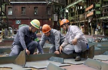 中尾社長(左)からアドバイスをもらう外国人労働者。現場では日本人が目を配れるようにヘルメットの色を分けている=佐世保市立神町、佐世保重工業構内