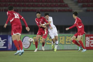 サッカーの2022年W杯アジア2次予選で、北朝鮮選手と競り合う韓国選手(中央右)=15日、平壌(韓国サッカー協会提供、AP=共同)