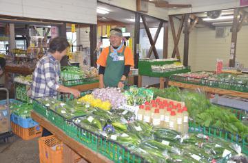 野菜が並ぶ前で出荷した農家と会話する谷津安男店長(右)=城里町御前山