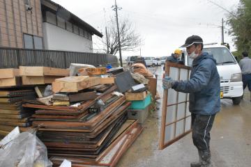 水に浸かり、使えなくなった家の中の物を通りに出す住民男性ら=19日午前、水戸市岩根町