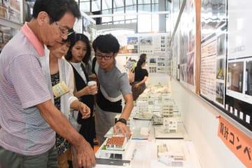 沖縄家作人NETがこれまでに提案した住宅模型を見て、理想とする家づくりの形を探る来場者=19日、宜野湾市・沖縄コンベンションセンター