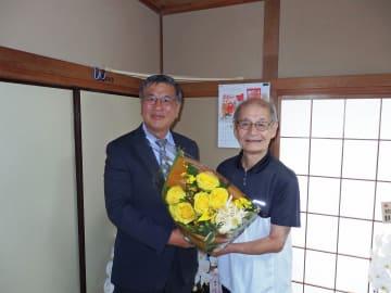 吉野さん(右)に花束を贈る鈴木市長=藤沢市内