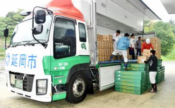 延岡市から届いたミネラルウオーターを運ぶいわき市職員ら