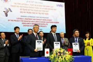 NEC製の地球観測衛星打ち上げで、住商とVNSCが契約を交わした=18日、ハノイ