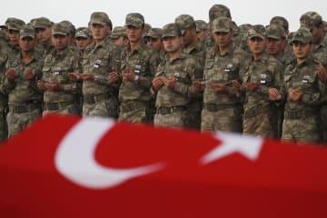 トルコ・シャンルウルファの空港で、シリアのクルド人側との戦闘で死亡した兵士のひつぎに祈りをささげるトルコ軍(AP=共同)