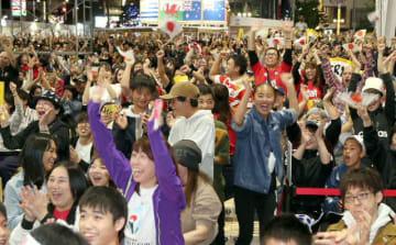 パブリックビューイングで日本の得点に喜ぶ人たち=20日夜、大分市府内町の祝祭の広場