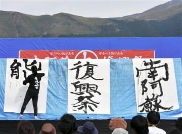「南阿蘇大復興祭」でパフォーマンスを披露する東海大書道部の学生=南阿蘇村