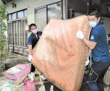 浸水した住宅から水にぬれたマットレスを運び出す部員たち