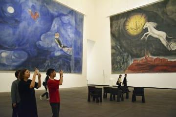 スマホやカメラをかざし、県立美術館のアレコホールで記念撮影する来場者=2018年8月